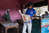 A subscriber of Khabar Lahariya reads his copy of this week's newspapers at his snacks shop in Manikpur, Chitrakoot, Uttar Pradesh, India on 6th December 2012.  Shanti used to be a wood gatherer, working with her parents since she was 3, and later carrying up to 100 kg of wood walking 12km from the dry jungle hills to her home to repack the wood which sold for 3 rupees per kg. After learning to read and write in an 8 month welfare course, at age 32, she became a reporter, joining Khabar Lahariya newspaper since its establishment in 2002, and making about 9000 rupees per month, supporting her family of 14 as the sole breadwinner. Photo by Suzanne Lee for Marie Claire France.