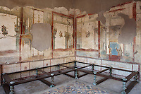 The Triclinium, probably used for lunches, a large room open to the garden, with walls painted on a white background with figures and plants and ornamental borders and floating figures of the seasons, in the Casa dell Efebo, or House of the Ephebus, Pompeii, Italy. This room is decorated in the Fourth Style of Roman wall painting, 60-79 AD, a complex narrative style. On the floor is a rare example of a coloured marble and glass mosaic patterned floor. This is a large, sumptuously decorated house probably owned by a rich family, and named after the statue of the Ephebus found here. Pompeii is a Roman town which was destroyed and buried under 4-6 m of volcanic ash in the eruption of Mount Vesuvius in 79 AD. Buildings and artefacts were preserved in the ash and have been excavated and restored. Pompeii is listed as a UNESCO World Heritage Site. Picture by Manuel Cohen