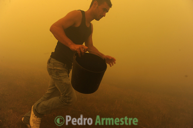 A man of Porqueira runs around the area where a fire burns in Porqueira, near A Coruña, on august 14, 2010, near Ourense.  Pedro ARMESTRE