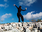 Young woman martial artist standing on rocks, practicing Kung Fu in the nature under blue sky. Ontario, Canada.