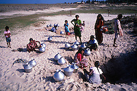 Sri Lanka. Women collect fresh drinking water from the shallow wells dug into the beach at Udappuwa. West Coast of the island.