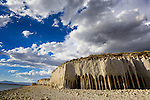 Delicate arches and deep caves formed by years of wind and waves pounding the east side of Crowley Lake along 395 near Mammoth Lakes, California. Lowering water levels have left a beach of round stones from the collapsed pillars.