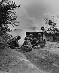 Marine gunners firing a round from a 37mm gun at entrenched Japanese troops along a dirt road on Saipan, What apears to be peep holes in the gun shield are bullet holes from enemy fire.