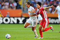 Carli Lloyd (l) of Team USA and Jo Yun Mi of North Korea during the FIFA Women's World Cup at the FIFA Stadium in Dresden, Germany on June 28th, 2011.