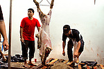 "Men butcher sheep that have been killed for Eid al-Adha - or ""Festival of Sacrifice"" - an important religious holiday celebrated by Muslims worldwide to commemorate the willingness of Abraham (Ibrahim) to sacrifice his son Ishmael (Isma'il) as an act of obedience to God, before God intervened to provide him with a sheep to sacrifice instead...Those Muslims who can afford to, sacrifice their best domestic animals (usually a cow, but can also be a camel, goat, sheep or ram depending on the region) as a symbol of Abraham's willingness to sacrifice his only son. The sacrificed animals, called U?hiyyah, have to meet certain age and quality standards or else the animal is considered an unacceptable sacrifice. ..The meat from the sacrificed animal is divided into three parts. The family retains one third of the share; another third is given to relatives, friends and neighbors; and the other third is given to the poor and needy. The regular charitable practices of the Muslim community are demonstrated during Eid al-Adha by concerted efforts to see that no impoverished person is left without an opportunity to partake in the sacrificial meal during these days."