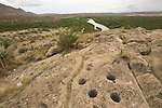 Mortar holes left by Native Americans in rock outcrop overlooking Rio Grande, at Bouquillas Canyon, Big Bend National Park, Texas.