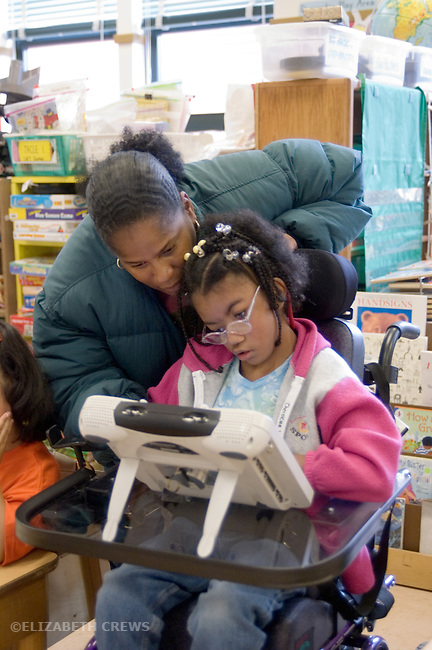 Oakland CA Developmentally disabled primary school student and teacher working with AAC (Alternative augmentative communication) devices in special education classroom  MR