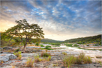 On a peaceful summer morning in the Texas Hill Country, this image attempts to capture the essence of Pedernales Falls State Park. Quiet, serene, and magical in the morning, this Texas state park offers a chance to escape the rush of the city. Located about 30 minutes outside of Austin, Texas, this little patch of wilderness is easily accessible. The irony is that while I do come out here frequently for sunrises, I rarely see anyone. My only company are the deer, turkey, foxes and coyotes, birds, and even the occassional skunks and feral pigs.