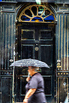 An elderly woman holding an umbrella walking past a large old doorway in Bury St Edmunds.