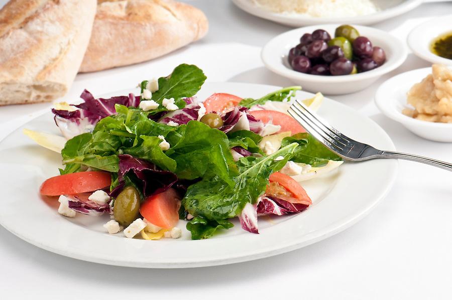 Close up of salad made of arugula, radicchio, belgian endive, bibb lettuce, tomatoes, and olives.