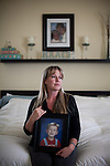 April Brune poses for a portrait while holding a portrait of her son Ryan on her bed in her Reno, Nevada home, February 3, 2014. Ryan Brune died from leukemia he was diagnosed with while they lived in Fallon, Nevada.