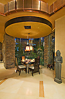 Dining table and chairs are seen under round ceiling with copper facia