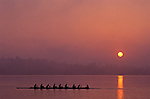 Crew on Union Bay silhouetted at sunrise with oars in water Seattle Washington USA