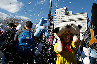 A woman covers her head while people take part in the pillow fight at Washington Square in New York. 04.04.2015. Eduardo MunozAlvarez/VIEWpress.