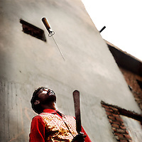 Krishan the Juggler juggles swords in the Kathputli Colony. Located in northwest Delhi, Kathputli is inhabited by approximately 2,000 performing artists, practicing traditional art forms such as marionette puppetry, juggling, magic, acrobatics, dance and music. Many have travelled all over the world showcasing their abilities, but they still choose to remain living in this slum, which is one of the most impoverished in the city.