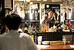 A waiter serves beer at craft beer bar Ushitora in Shimokitazawa, Setagaya Ward, Tokyo, Japan..Photographer: Robert Gilhooly