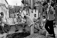 State of Palestine. West Bank. Balata Camp. Palestinian refugees. Daily life. A family watches a young man digging a hole with a pickaxe in order to bury chickens' droppings under the ground. Balata Camp is a Palestinian refugee camp established in the northern West Bank in 1950, adjacent to the city of Nablus. It is the largest refugee camp in the West Bank. Balata Camp is densely populated with 30,000 residents in an area of 0.25 square kilometers. In 1991, Balata Camp was living under Isreal's occupation and rules as part as the Occuppied Territories. In the 1980s and 1990s, Balata residents played a leading role in the uprisings known as the First Intifada and the Second Intifada. Balata Camp is since 1993 under palestinian authority, located in the A zone. The Palestinian National Authority (PA or PNA) was the interim self-government body established to govern Areas A and B of the West Bank as a consequence of the 1993 Oslo Accords. Following elections in 2006, its authority had extended only in areas A and B of the West Bank. Since January 2013, the Fatah-controlled Palestinian Authority uses the name State of Palestine on official documents. © 1991 Didier Ruef