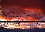 Farmingdale, New York, USA. November 26, 2016.  Sunset in truck parking area in industrial storage area of Farmingdale in Long Island. Barbed wire tops chain link fence separating properties. Black barb razor wire atop chain link fence during sunset, USA