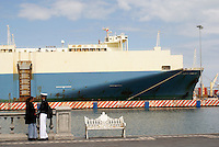 Mexican sailor and his girlfriend standing in front of a huge ship used to carry automobiles, port of Veracruz, Mexico