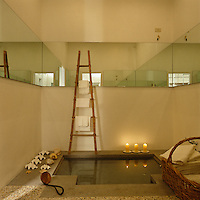 A band of mirrors enhances the space and light in this bathroom while a bamboo ladder at the edge of the sunken bath is used for hanging towels