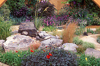 Ornamental grasses in a Feng Shui garden Zen meditation design, dark leaved purple black foliage dahlias, Primula, using rock stone boulders in naturalistic landscape, curved walkway path, wall, climbing plants and flowers, varied and mixed plants types, for personal styl in the backyard landscape