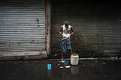 A man bathes in the street in Kolkata, West Bengal, India.