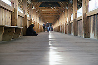A female beggar sits on the floor of the Kapellbrücke (Chapel Bridge) in Lucerne, awaiting passers-by