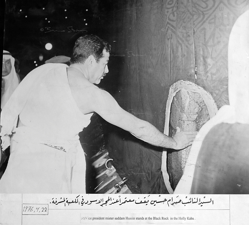 """Mecca, Saudi Arabia, April 22, 1976.Saddam Hussein touching the Black Rock of the Kaba during his """"Hajj """" pilgrimage in Mecca..Photograph recovered by Bruno Stevens in the looted """"Triumphant Leader"""" museum in Baghdad, entirely dedicated to the glory of Saddam Hussein."""