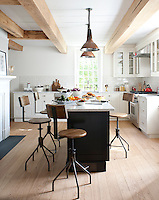 Vintage barn lights hang above the kitchen island around which is grouped a collection of vintage metal bar stools