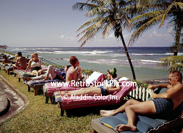 People relaxing on lounge chair on beach at the Flamboyan Hotel in Puerto Rico. 1960's