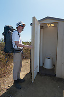 My friend holds open the door to the pit toilet so you, my kind readers, can see what it's like.  Clean, low-smell, and when we were there stocked with toilet paper.  Note: this photograph has had an element unrelated to the subject of the photograph (documentation of the condition of the toilet) removed in Photoshop.