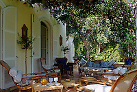 A variety of comfortable garden chairs and sun-loungers grouped on a tiled terrace in the dappled shade of a bougainvillea