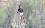 A girl walks to school across a suspension bridge over the Trishuli River near the village of Buttar in the Gorkha District of Nepal.