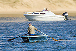 A small-scale fisher rows his wooden boat in front of an expensive  recreational ski-boat, Sundays River Estuary, Algoa Bay, Eastern Cape, South Africa