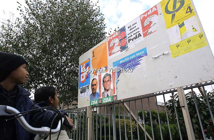 """Foto: VidiPhoto..OPHEUSDEN - De verkiezingsstrijd in de Midden-Betuwe is losgebarsten. Door de gemeentelijke herindeling moeten woensdag 31 oktober de inwoners van drie gemeenten (Dodewaard, Kesteren en Echteld) naar de stembus. De strijd gaat voornamelijk tussen SGP (nu de grootste) en PvdA. Vooral in Opheusden (gemeente Kesteren) zit de haat tussen beiden diep. Op dit verkiezingsbord laten de socialisten fijntjes weten dat vrouwen bij de PvdA """"ook"""" mee mogen doen."""