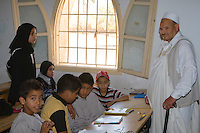 """Surman, Libya.  Boys and Girls Memorizing the Koran in the Madrasa of Sidi Rashid al-Galili.  They study under the supervision of Bashir, a """"muqri"""".  He wears the traditional """"holi"""" or """"jard"""", a white cloak.  Young girls wear the traditional Libyan head scarf.  Boys may wear traditional garments, but western or European sport shirts or T-shirts are more popular."""
