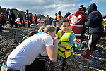 A volunteer helps remove a life jacket from a refugee girl who just arrived on a beach near Molyvos, on the Greek island of Lesbos, on October 31, 2015.  The girl and her family, part of a boatful of refugees that arrived from Turkey, were received by local and international volunteers, then proceeded on their way toward western Europe. The boat was provided by Turkish traffickers to whom the refugees paid huge sums to arrive in Greece.
