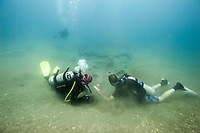Two SCUBA divers take a measurement of a 17th century shipwreck. (Model Released)