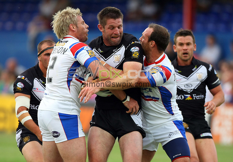 PICTURE BY VAUGHN RIDLEY/SWPIX.COM - Rugby League - Super League - Wakefield v Hull FC - Hearwell Stadium, Wakefield, England - 10/07/10...Copyright - Simon Wilkinson - 07811267706...Wakefield's Glenn Morrison and Paul Johnson tackle Hull FC's Peter Cusack.