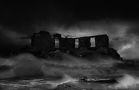 Waves breaking on ruins in a bad storm in the middle of the night.