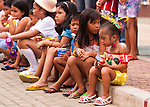 Children wearing festive buri clothes and decorations watch the end of the Sampaloc Bulihan Fiesta's opening parade in April 2012.  (Sampaloc, Quezon Province, the Philippines.)