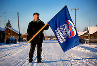 Nikifor Alfonski, head of the Bedime village in Yakutia, holds a United Russia flag, the party that supports Prime Minister Putin and President Medvedev...