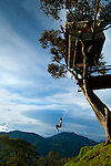 """A tourist is enjoying the """"Swing At The End Of The World"""", an adventure destination in Banos, Ecuador.  The swing carries the swinger out over a deep mountainous canyon and is attached to a treehouse called La Casa del Arbol.  The treehouse was constructed many years ago to monitor the Tungurahua Volcano."""