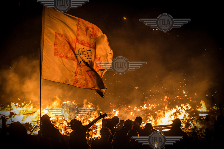 Protesters hodling up a flag stand next to burning barricades near Maidan Nezalezhnosti (Independence Square), renamed EuroMaidan by protesters since November 2013. Protests against the government of President Viktor Yanukovych were sparked on 21 November 2014 by the Ukrainian government's decision to suspend preparations for the signing of an association agreement with the European Union that would have increased trade with the EU. Some believe that the U-turn came about as a result of pressure from President Putin of Russia who wants Ukraine to join a customs union with itself, Kazakhstan and Belarus. Russia offered 15 billion dollars of soft loans and reduced price gas to Ukraine at the same time as discussions with the EU were taking place. After weeks of protests and a number of deaths, Prime Minister Mykola Azarov and the entire cabinet resigned. Protesters are holding out, however, for President Yanukovych to resign and continue to occupy public buildings and squares to put pressure on the president. On 18 February, after Yanukovych's party scuppered a move to change the constitution to reduce the powers of the president, renewed fighting between protesters and police broke out and had cost the lives of around 80 people by Friday 21st February.
