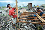 Marnel Leporada (left) and Randy Espina work to build a temporary house in Tanauan, a city in the Philippines province of Leyte that was hit hard by Typhoon Haiyan in November 2013. The storm was known locally as Yolanda. Their families have received emergency assistance from the United Methodist Committee on Relief, a member of the ACT Alliance. UMCOR is working with city officials to help residents here build permanent houses to replace those they lost in the storm.