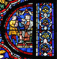 Noah drinking wine, served to him by his son, which will lead to his drunkenness, from the Life of Noah stained glass window, 13th century, in the nave of Chartres cathedral, Eure-et-Loir, France. Chartres cathedral was built 1194-1250 and is a fine example of Gothic architecture. Most of its windows date from 1205-40 although a few earlier 12th century examples are also intact. It was declared a UNESCO World Heritage Site in 1979. Picture by Manuel Cohen