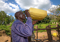 """Alphonse Elic, 51, stops twice a day at the Ageci village borehole on his six kilometer trek to school, almost 2 hrs each way, where he is an English teacher at the primary school. """"You have helped me, he says. Every day I stop here to drink and I am so happy to have water on my journey to and from school…"""" This well serves about 500 people."""