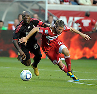 AC Milan midfielder Clarence Seedorf (10) battles for the ball with Chicago Fire midfielder Logan Pause (12).  AC Milan defeated the Chicago Fire 1-0 at Toyota Park in Bridgeview, IL on May 30, 2010.