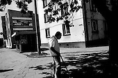 Ruda, Poland.August 1997.With the Marlboro man on the wall in the background an elderly man begins his walk home from Sunday church service..
