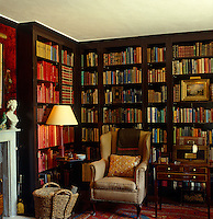 A large comfortable armchair upholstered in checked fabric sits in a corner of this booklined library